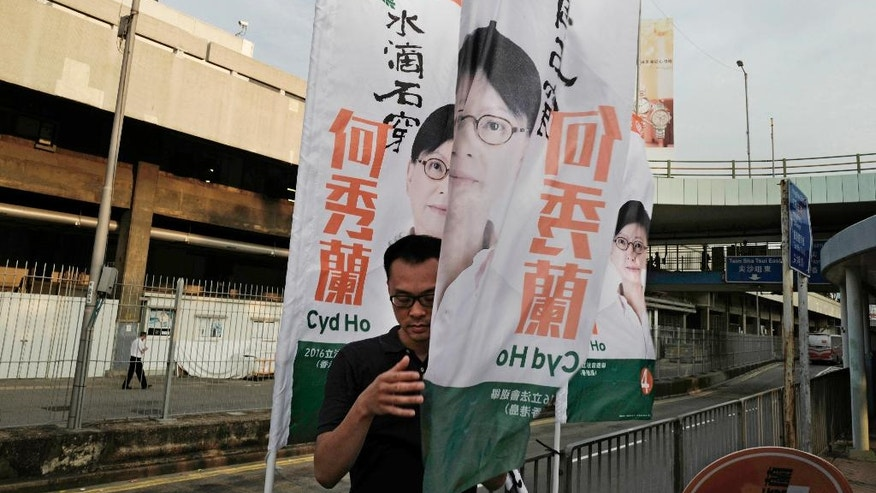 In this Aug. 26, 2016 photo, a supporter hangs up election banners for pro-democracy candidate Cyd Ho in Hong Kong. Hong Kongers head to the polls Sunday, Sept. 4, 2016 to choose candidates for the semiautonomous city's legislature, in the first major election since 2014's pro-democracy street protests. That movement drew world attention to the former British colony's struggle over stunted democratic development under Chinese rule and paved the way for a burgeoning independence movement that's complicating the upcoming vote. (AP Photo/Vincent Yu)