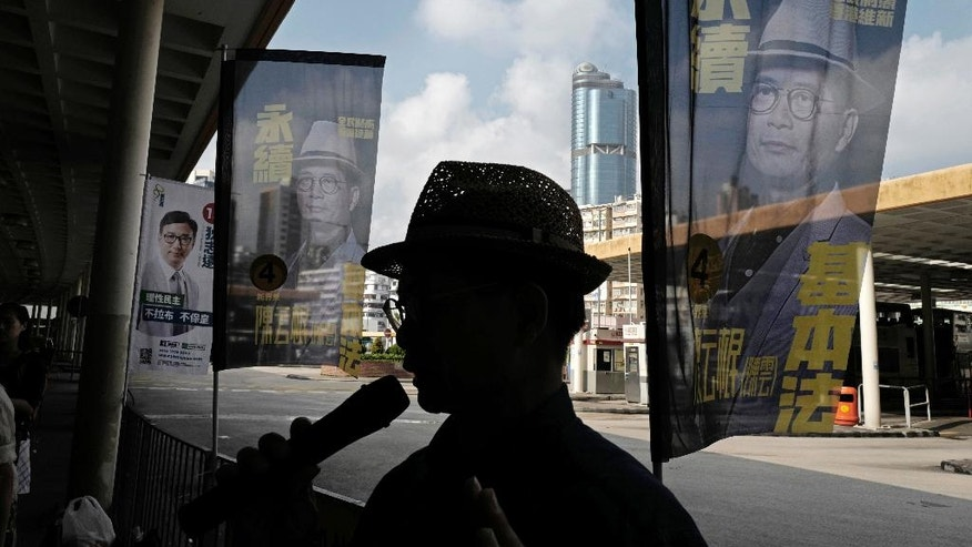 """In this Aug. 25, 2016 photo, Horace Chin, a candidate in Hong Kong's upcoming legislative elections who's known as the """"godfather of localism,"""" is flanked by his campaign banners in Hong Kong. Hong Kongers head to the polls Sunday, Sept. 4, 2016 to choose candidates for the semiautonomous city's legislature, in the first major election since 2014's pro-democracy street protests. That movement drew world attention to the former British colony's struggle over stunted democratic development under Chinese rule and paved the way for a burgeoning independence movement that's complicating the upcoming vote. (AP Photo/Vincent Yu)"""