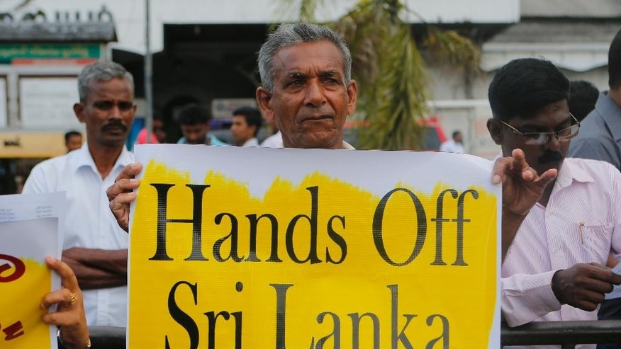A member of opposition political party National Freedom Front, which is supporting former president Mahinda Rajapaksa holds a placard during a protest against current Sri Lanka tour of U.N. Secretary General Ban Ki-moon in Colombo, Sri Lanka, Thursday, Sept. 1, 2016. United Nations Secretary-General Ban Ki-moon began a visit to Sri Lanka on Wednesday during which he is expected to discuss post-civil war reconciliation and human rights accountability with the country's leaders. (AP Photo/Eranga Jayawardena)