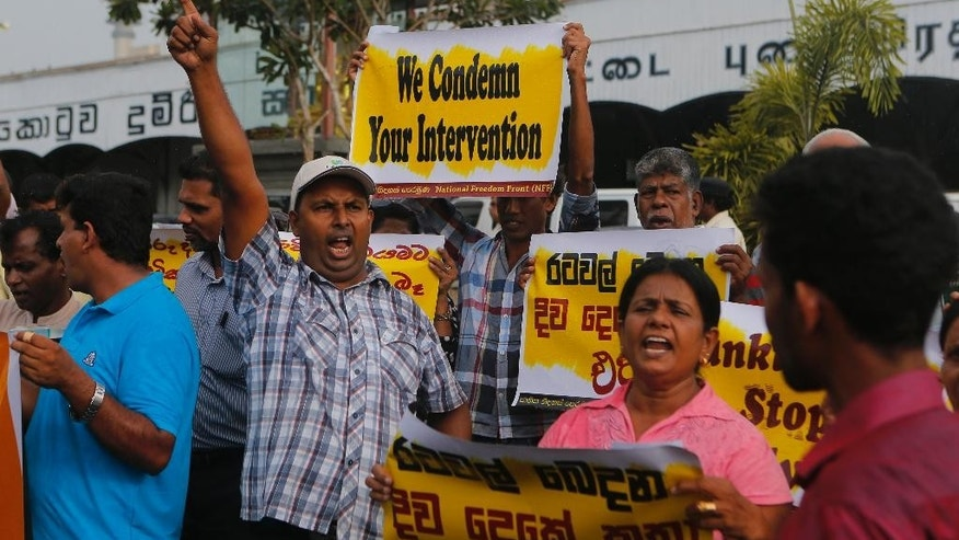 "Members of opposition political party National Freedom Front, which is supporting former president Mahinda Rajapaksa shout slogans holding placards during a protest against current Sri Lanka tour of U.N. Secretary General Ban Ki-moon in Colombo, Sri Lanka, Thursday, Sept. 1, 2016. United Nations Secretary-General Ban Ki-moon began a visit to Sri Lanka on Wednesday during which he is expected to discuss post-civil war reconciliation and human rights accountability with the country's leaders. Placards on front right and back read "" No to double standard talks dividing countries"" in Sinhalese.(AP Photo/Eranga Jayawardena)"
