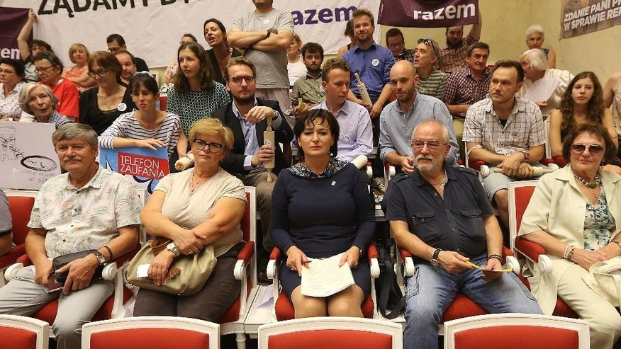 Representatives of left-wing organizations and groups of property owners and tenants watch broadcasts of Warsaw Mayor Hanna Gronkiewicz-Waltz during an extraordinary session of the Warsaw city council in Warsaw, Poland, on Thursday, Sept.1, 2016. The mayor said that irregularities in the restitution of seized Warsaw property to private owners were the fault of all political teams who have ruled the capital city under democracy since 1990, but stressed she was the one who successfully pushed for regulations that will take effect this month and will eliminate some of the bad practices. (AP Photo/Czarek Sokolowski)