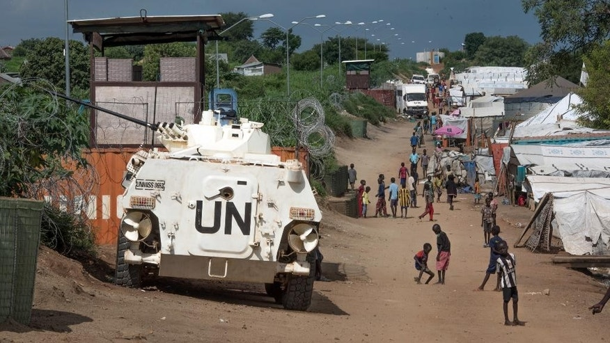 FILE - In this Monday, July 25, 2016 file photo, some of the more than 30,000 civilians sheltering in a United Nations base in South Sudan's capital Juba  walk by an armored vehicle and a watchtower manned by Chinese UN peacekeepers. The U.N. Security Council is expected to arrive in South Sudan on Friday, Sept. 2, 2016 for a three-day visit to the troubled nation on the edge of renewed civil war. (AP Photo/Jason Patinkin, File)