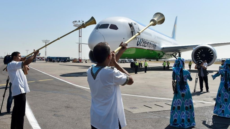 Performers dressed in Uzbek national costumes take part in a welcome ceremony of a new Boeing 787 Dreamliner that will be used by the national airway company, at the airport in Tashkent, Uzbekistan, Wednesday, Aug. 31, 2016. Uzbekistan's prime minister led the nation's Independence Day celebration Wednesday in the capital of Tashkent as President Islam Karimov remained hospitalized. (AP Photo)