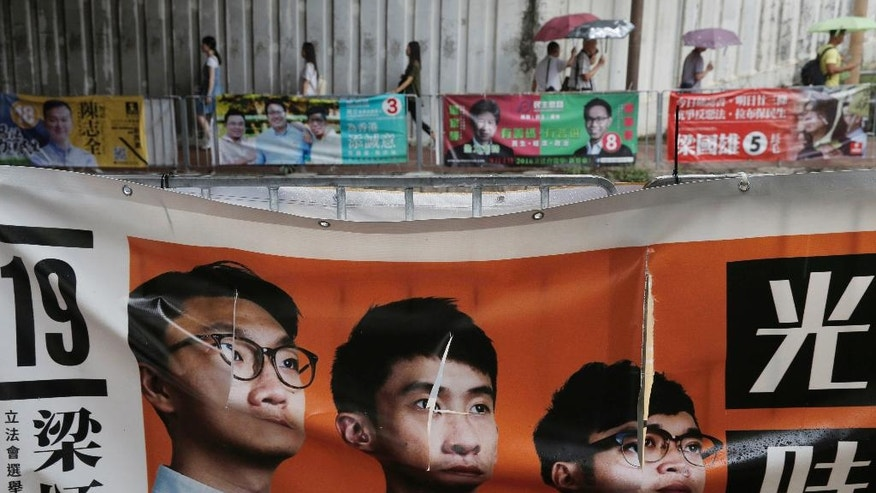 In this Friday, Sept. 2, 2016, photo, an election banner for radical activist candidate, from left, Edward Leung, Baggio Leung Chung-hang and Li Tung-sing are seen defaced days before legislative elections, in Hong Kong. Hong Kongers are heading to the polls Sunday in the first major election since 2014 pro-democracy street protests. A new crop of radical activists are challenging both pro-Beijing rivals and Hong Kong's mainstream pro-democracy parties for seats in the Legislative Council. A series of vandalized posters are a sign that the elections are the most contentious since the 1997 British handover of the city to China. (AP Photo/Kin Cheung)