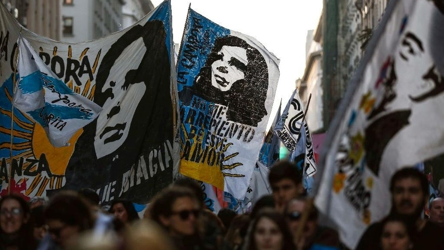 Demonstrators waving flags featuring images of former President Cristina Fernandez and late president Nestor Kirchner, march towards the Plaza de Mayo, in Buenos Aires, Argentina, Friday, Sept. 2, 2016. Closing out three days of demonstrations that included road blockages across the country, columns of protesters converged in front of the presidential palace to voice their anger against government job cuts, the elimination of subsidies and other policies of Argentina's President Mauricio Macri. (AP Photo/Agustin Marcarian)