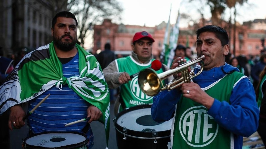 State workers, taking part in an anti-government protest, play drums and a trumpet at the Plaza de Mayo, in Buenos Aires, Argentina, Friday, Sept. 2, 2016. Closing out three days of demonstrations that included road blockages across the country, columns of protesters converged in front of the presidential palace to voice their anger against government job cuts, the elimination of subsidies and other policies of Argentina's President Mauricio Macri. (AP Photo/Agustin Marcarian)