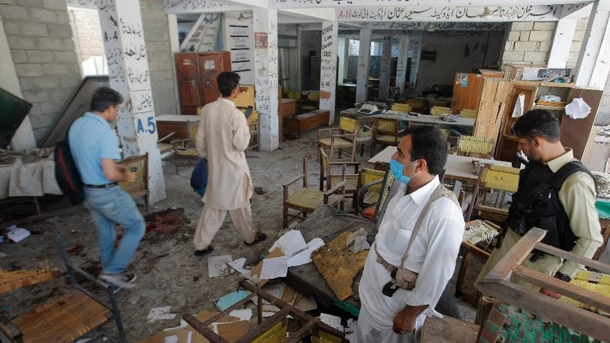 Pakistani officials examine a site of bombing in Mardan, Pakistan, Friday, Sept. 2, 2016. Northwestern Pakistan was struck by two separate militant attacks on Friday, when gunmen wearing suicide vests stormed a Christian colony near the town of Peshawar, killing one civilian, and a suicide bomb attack on a district court in the town of Mardan killed scores of people and wounded many. (AP Photo/Mohammad Sajjad)