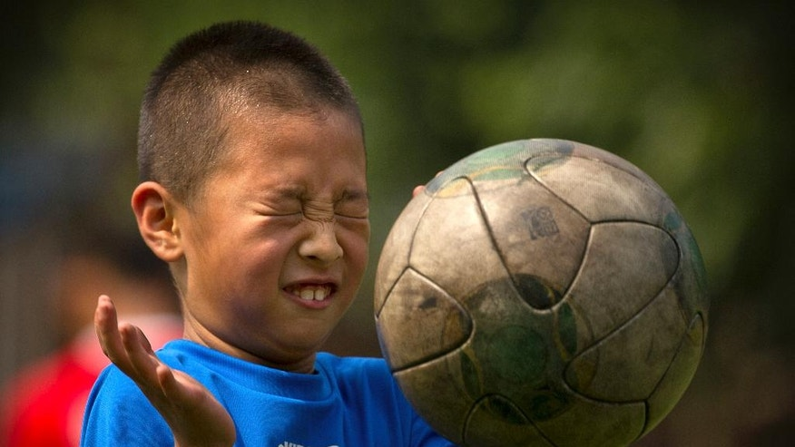 In this Wednesday, July 6, 2016, photo, a boy reacts as he attempts to head the ball during a soccer training camp at Ritan Middle School in Beijing, China. China is mobilizing under President Xi Jinping's drive to overhaul football in China and turn its team from a national embarrassment into a World Cup winner by 2050. (AP Photo/Mark Schiefelbein)