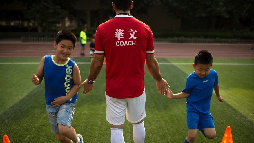 In this Wednesday, July 6, 2016, photo, boys high-five coach Juan Varela, center, as they run past him during an exercise drill at soccer training camp at Ritan Middle School in Beijing, China. China is mobilizing under President Xi Jinping's drive to overhaul football in China and turn its team from a national embarrassment into a World Cup winner by 2050. (AP Photo/Mark Schiefelbein)