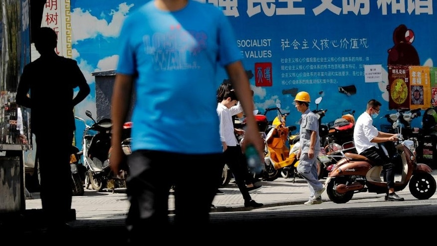 "People walk by scooters parked against a billboard displaying a Chinese government propaganda message in Beijing, Friday, Sept. 2, 2016. Leaders of the U.S., China and other big Group of 20 economies will be attending a two-day meeting this weekend, with the global economy expected to be one of the main discussion topics. China, the G-20 meeting's host, has made trade a major theme of the meeting while other governments also want to tackle climate change, cutting excess capacity in steel and limits on use of tax havens. The billboard reads ""Rich, Democracy, Civilization and Harmonious."" (AP Photo/Andy Wong)"