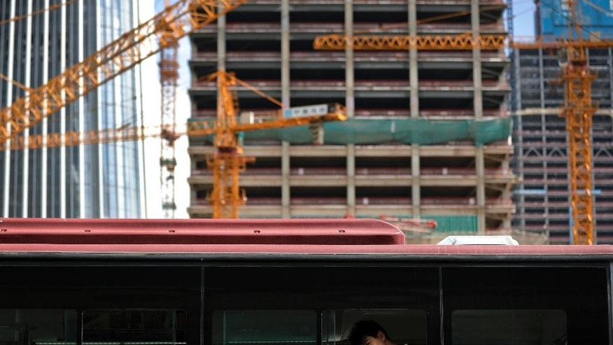 A man looks out from a bus as he goes by a construction site in Beijing, Friday, Sept. 2, 2016. Leaders of the U.S., China and other big Group of 20 economies will be attending a two-day meeting this weekend, with the global economy expected to be one of the main discussion topics. China, the G-20 meeting's host, has made trade a major theme of the meeting while other governments also want to tackle climate change, cutting excess capacity in in steel and limits on use of tax havens. (AP Photo/Andy Wong)