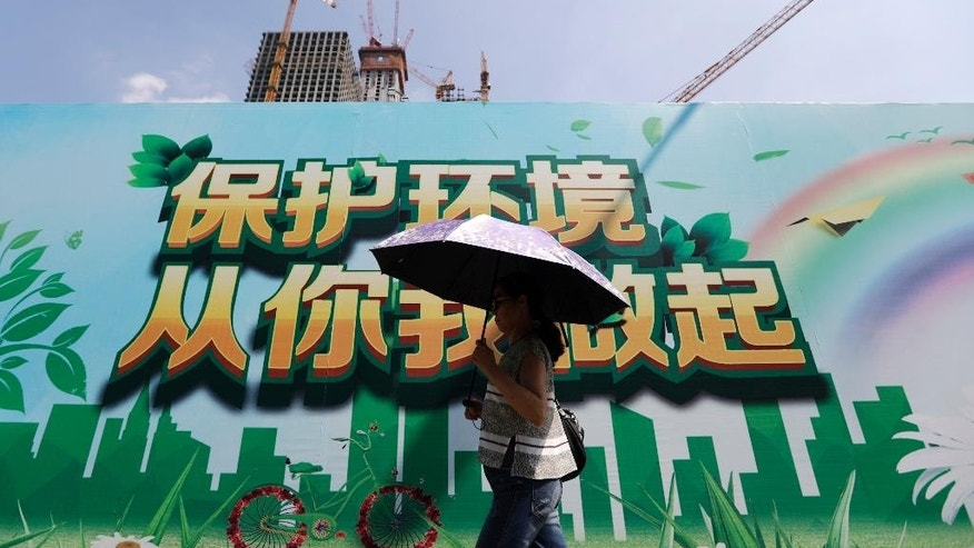 "A woman carrying an umbrella to protect from the sun as she walks past a billboard promoting environment protection on display near a construction site at the Central Business District of Beijing, Saturday, Sept. 3, 2016. China announced on Saturday that it has ratified the emissions-cutting agreement reached last year in Paris, giving a big boost to efforts to bring the accord into effect by the end of this year. The words on the billboard read ""Protect environment, start from you and me."" (AP Photo/Andy Wong)"