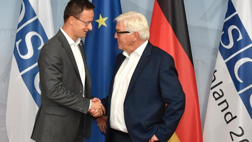 Hungary's Foreign Minister Peter Szijjarto, left, is greeted by German Foreign Minister Frank-Walter Steinmeier during the Informal OSCE Foreign Minister's Meeting in Potsdam, Germany, Thursday, Sept. 1, 2016. (John MacDougall/Pool Photo via AP)