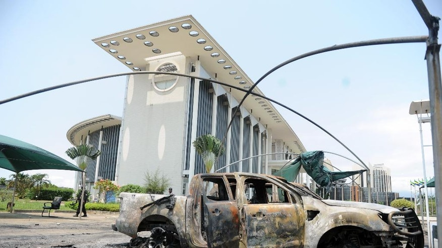 Burnt out cars are seen outside a government building, following an election protest in Libreville, Gabon, Thursday Sept. 1, 2016. Gabon's newly re-elected president sought to assert authority Thursday as the presidential guard attacked the opposition candidate's party headquarters overnight, killing at least one person and injuring more than a dozen amid fiery protests that have seen hundreds detained and the internet blocked. (AP Photo/Joel Bouopda)
