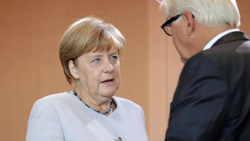 German Chancellor Angela Merkel, left, talks to German Foreign Minister Frank-Walter Steinmeier, right, during her arrival for the weekly cabinet meeting at the Chancellery in Berlin, Germany, Wednesday, Aug. 31, 2016. (AP Photo/Michael Sohn)