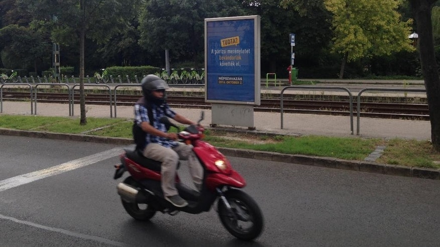 "In this Aug. 13, 2016 picture a person on motorbike passes a government poster promoting the Oct. 2 referendum against any EU quotas to resettle migrants. reading ""Did you know? The Paris attacks were carried out by immigrants."" in Budapest.  A month ahead of a referendum seeking popular support for its opposition to European Union migrant quotas, the Hungarian government's relentless anti-migrant campaign is inescapable and shows no sign of letting up. (AP Photo/ Pablo Gorondi)"