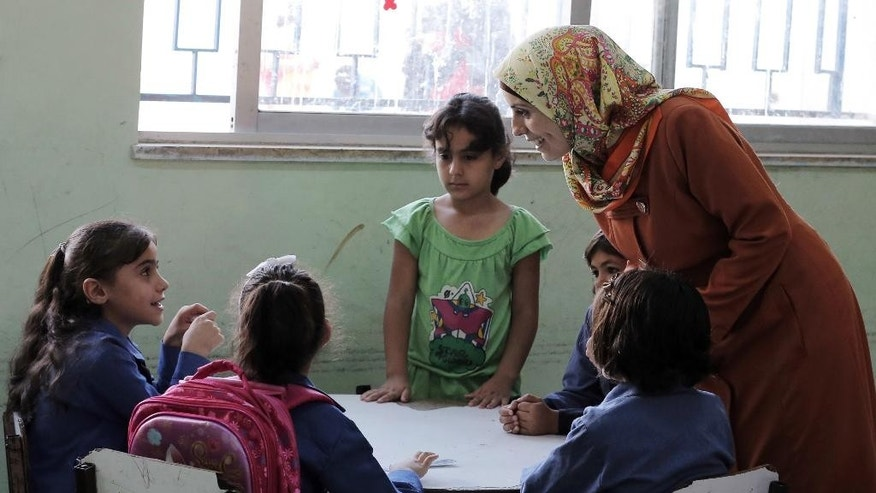 "In this Thursday, Sept. 1, 2016 photo, a Jordanian teacher talks to Syrian refugee students at school in Amman, Jordan. Jordan says it is opening its schools to all Syrian refugee children, starting this week, by adding more shifts and hiring more teachers. It is part a deal with donor countries to make life better for refugees and discourage them from migrating onward, in exchange for aid and trade benefits. Last year, more than 90,000 Syrian children in Jordan weren't getting an education, along with hundreds of thousands in neighboring refugee host countries, prompting warnings of a ""lost generation.""(AP Photo/Ahmad Alameen)"