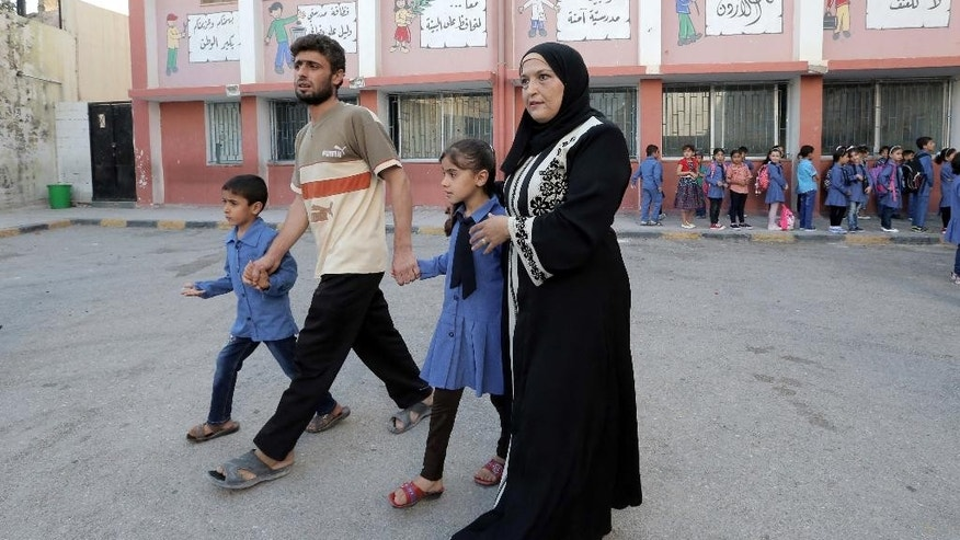"In this Thursday, Sept. 1, 2016 photo, a Syrian refugee family brings their children to school in Amman, Jordan. Jordan says it is opening its schools to all Syrian refugee children, starting this week, by adding more shifts and hiring more teachers. It is part a deal with donor countries to make life better for refugees and discourage them from migrating onward, in exchange for aid and trade benefits. Last year, more than 90,000 Syrian children in Jordan weren't getting an education, along with hundreds of thousands in neighboring refugee host countries, prompting warnings of a ""lost generation.""(AP Photo/Ahmad Alameen)"