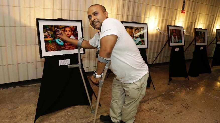 In this Aug. 27, 2016 photo, Gautam Lewis talks about an image displayed at his photography exhibition in connection with Mother Teresa's canonization in Kolkata, India. For Lewis, a polio victim abandoned by his parents as a child and rescued by Mother Teresa, the nun is already a saint. At seven, he was adopted from an orphanage run by the Missionaries of Charity, the order set up by Mother Teresa, and moved first to New Zealand and later England. Lewis, 39, now runs a flying school for people with disabilities in the United Kingdom. (AP Photo/Bikas Das)