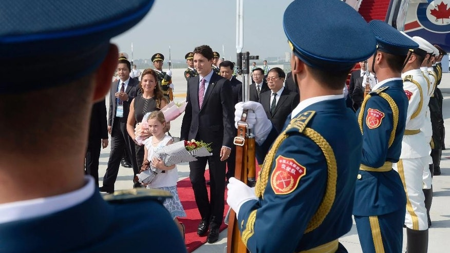 An honor guard of the People's Liberation Army stand at attention as Canadian Prime Minister Justin Trudeau, his wife Sophie Gregoire and daughter Ella-Grace arrive in Hangzhou, China, Saturday, Sept. 3, 2016. (Adrian Wyld/The Canadian Press via AP)