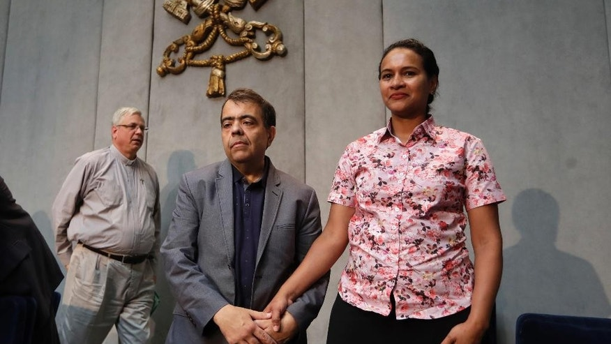 From left, Rev. Brian Kolodiejchuk, postulator of the cause of beatification and canonization of Mother Teresa, Marcilio Andrino, and his wife Fernanda Nascimento Rocha pose for photographers at the end of a press conference at the Vatican, Friday, Sept. 2, 2016. Andrino's cure of a viral brain infection, declared a miracle by Pope Francis earlier this year, was the final step needed to declare Mother Teresa a saint. (AP Photo/Alessandra Tarantino)