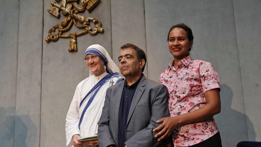From left, Sr. Mary Prema Pierick, Superior General of the Missionaries of Charity, Marcilio Andrino, center and his wife Fernanda Nascimento Rocha pose for photographers at the end of a press conference at the Vatican, Friday, Sept. 2, 2016. Andrino's cure of a viral brain infection, declared a miracle by Pope Francis earlier this year, was the final step needed to declare Mother Teresa a saint. (AP Photo/Alessandra Tarantino)