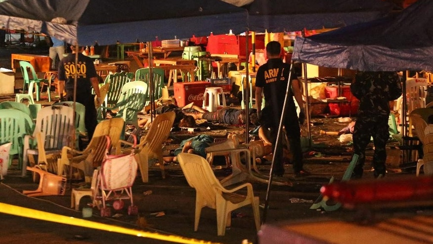 Philippine police officers stand beside bodies of victims after an explosion at a night market that has left about 10 people dead and wounded several others in southern Davao city, Philippines late Friday Sept. 2, 2016. Regional military commander Lt. Gen. Rey Leonardo Guerrero says it was not immediately clear what caused the explosion late Friday. (AP Photo/Manman Dejeto)