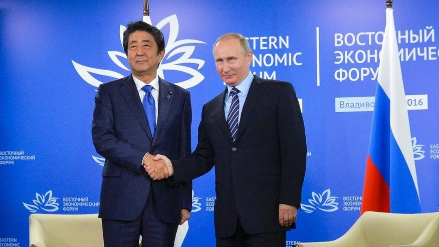 Russian President Vladimir Putin, right, and Japanese Prime Minister Shinzo Abe shake hands as they pose for a photo during their meeting in Vladivostok, Russia, Friday, Sept. 2, 2016. (Alexei Druzhinin, Sputnik, Kremlin Pool Photo via AP)