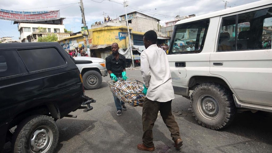 The body of slain Spanish nun Isabelle Sola Matas is carried away by morgue workers, after she was attacked while driving her car in downtown Port-au-Prince, Haiti, Friday, Sept. 2, 2016. Local judge Noel Jean Brunet said that two men on a motorcycle drove by and killed the 51-year-old Roman Catholic nun while she was driving. Matas worked at St. Joseph church where she directed a program providing people with prosthetic limbs. (AP Photo/Dieu Nalio Chery)