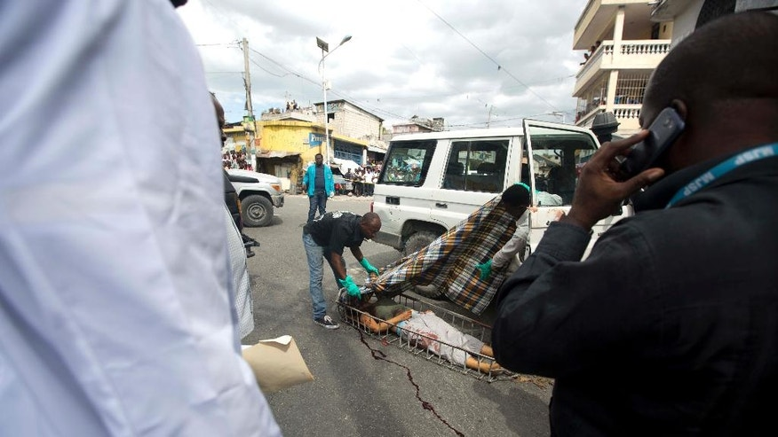 Morgue workers cover the body of slain Spanish nun Isabelle Sola Matas after she was attacked in her car in downtown Port-au-Prince, Haiti, Friday, Sept. 2, 2016. Local judge Noel Jean Brunet said that two men on a motorcycle drove by and killed the 51-year-old Roman Catholic nun while she was driving. Matas worked at St. Joseph church where she directed a program providing people with prosthetic limbs. (AP Photo/Dieu Nalio Chery)