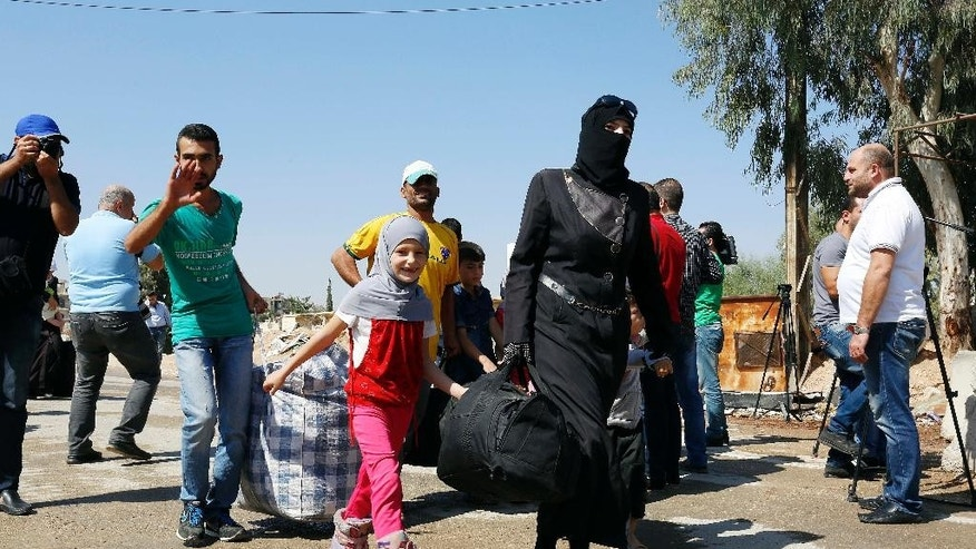 Syrians leave the Moadamiyeh suburb of Damascus, Syria, on Friday, Sept. 2, 2016. Dozens of Syrians living in a besieged rebel-held suburb of the capital, Damascus, have begun evacuating the area following a deal struck with the government that grants amnesty to gunmen and restores state control. (AP Photo)