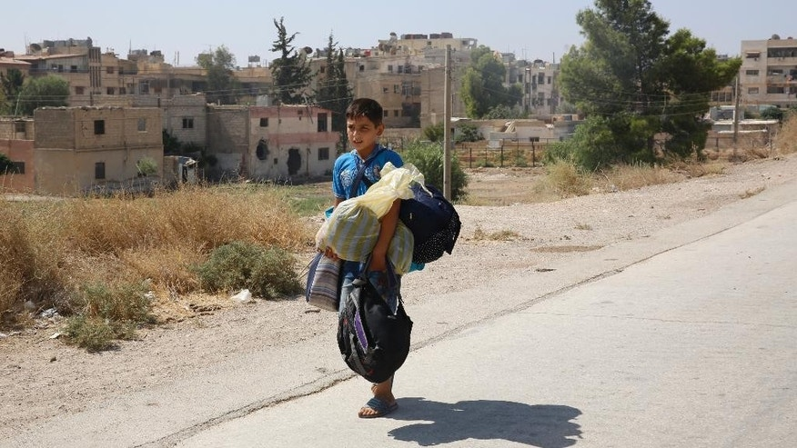 A boy carries his belongings as he leaves the Moadamiyeh suburb of Damascus, Syria, on Friday, Sept. 2, 2016. Dozens of Syrians living in a besieged rebel-held suburb of the capital, Damascus, have begun evacuating the area following a deal struck with the government that grants amnesty to gunmen and restores state control. (AP Photo)