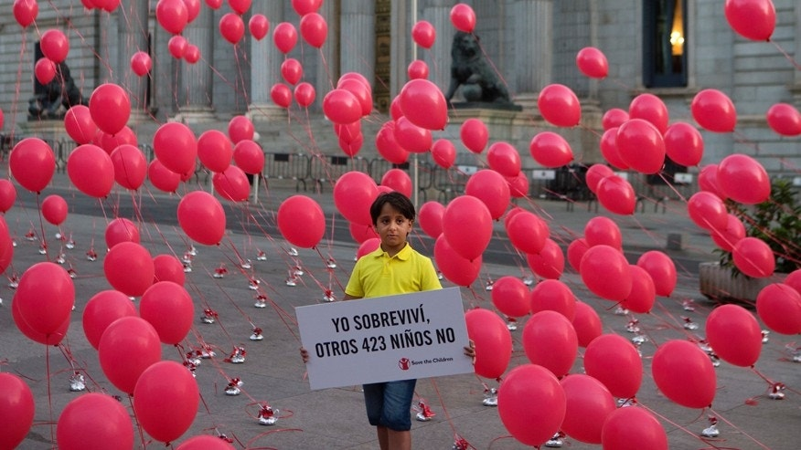 "Zaid, an eight-year-old Syrian refugee, now living in Spain, poses with a sign reading in Spanish: ""I survived, 423 other children did not"" in front of the Spanish parliament in Madrid, Spain, Thursday, Sept. 1, 2016. The symbolic protest was to highlight the plight of refugee children coinciding with the anniversary of the death of three year old refugee Aylan Kurdi, who was found dead on a beach in September 2015 near the Turkish resort of Bodrum."
