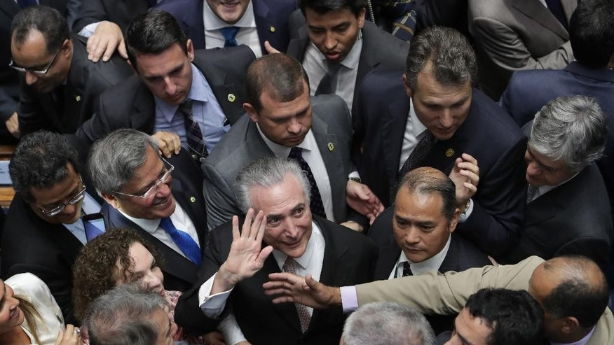 In this Wednesday, Aug. 31, 2016 photo, Brazil's President Michel Temer, center, is surrounded by senators as he arrives to take the presidential oath at the National Congress, in Brasilia, Brazil. Several dozen of the lawmakers who voted earlier in the day to remove President Dilma Rousseff are under investigation in the scandal involving billions of dollars of kickbacks. Rousseff has charged that corrupt lawmakers wanted her out to halt the Petrobras probe. But if the intention was to sweep the probe under the rug, it's too late, say law professors, corruption experts and political analysts. (AP Photo/Eraldo Peres)