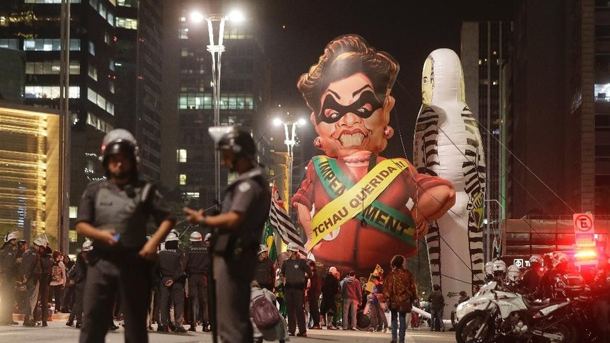 "In this Wednesday, Aug. 31, 2016 photo, police officers stand next to a large inflatable doll in the likeness of Brazil's ousted President Dilma Rousseff wearing a presidential sash with the words in Portuguese; ""Goodbye dear"" during a rally to celebrate her impeachment in Sao Paulo, Brazil. Rousseff became the biggest casualty of a massive corruption probe that is roiling Latin America's largest country, even though she was never personally implicated in the scheme. Nearly one third of Brazilians see corruption as the nation's biggest problem, a higher percentage than for any other issue, according to a July poll by Datafolha. Since early 2015, more than 2 million people have signed a petition from the attorney general's office to introduce new laws and levy harsher sentences for corrupt public servants.  (AP Photo/Andre Penner)"