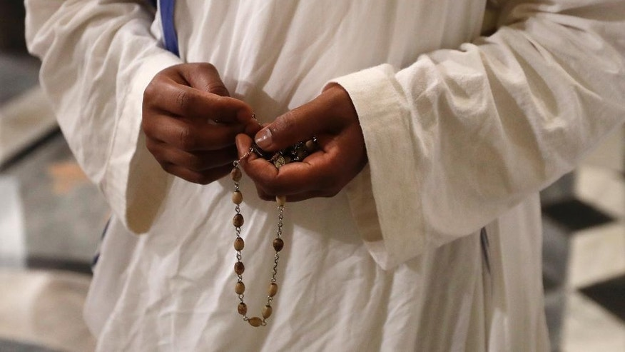 A nun of Mother Teresa's Missionaries of Charity holds a rosary during a vigil of prayer in preparation for the canonization of Mother Teresa in the St. John in Latheran Basilica at the Vatican, Friday, Sept. 2, 2016. (AP Photo/Gregorio Borgia)