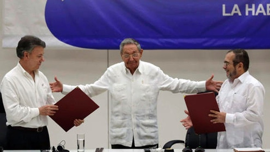 FILE - In this June 23, 2016 file photo, Cuba's President Raul Castro, center, motions to bring together Colombian President Juan Manuel Santos, left, and Commander of the Revolutionary Armed Forces of Colombia or FARC, Rodrigo Londono, better known as Timochenko or Timoleon Jimenez, during a signing ceremony of a cease-fire and rebel disarmament deal, in Havana, Cuba. Santos announced Friday, Sept. 2, 2016, that he will sign a peace accord with the FARC on Sept. 26. in Cartagena. (AP Photo/Ramon Espinosa, File)