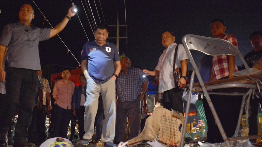 "In this photo released by Malacanang Palace Presidential Communications Operations Office Presidential Photographers Division, Philippine President Rodrigo Duterte, second left, visits the site of Friday night's explosion that killed more than a dozen people and wounded several others at a night market in Davao city, his hometown, Saturday, Sept. 3, 2016 in southern Philippines. Duterte declared a nationwide ""state of lawlessness"" Saturday after suspected Abu Sayyaf extremists detonated a bomb at the market. (Robinson Ninal/Malacanang Palace Presidential Communications Operations Office Presidential Photographers Division via AP)"