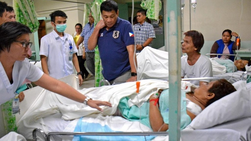 "In this photo released by Malacanang Palace Presidential Communications Operations Office Presidential Photographers Division, Philippine President Rodrigo Duterte, center, visits a hospital where victims of Friday's explosion were brought in from a night market in Davao city, his hometown, Saturday, Sept. 3, 2016 in southern Philippines. in Davao city, his hometown, Saturday, Sept. 3, 2016 in southern Philippines. Duterte declared a nationwide ""state of lawlessness"" Saturday after suspected Abu Sayyaf extremists detonated a bomb at the market. (Robinson Ninal/Malacanang Palace Presidential Communications Operations Office Presidential Photographers Division via AP)"