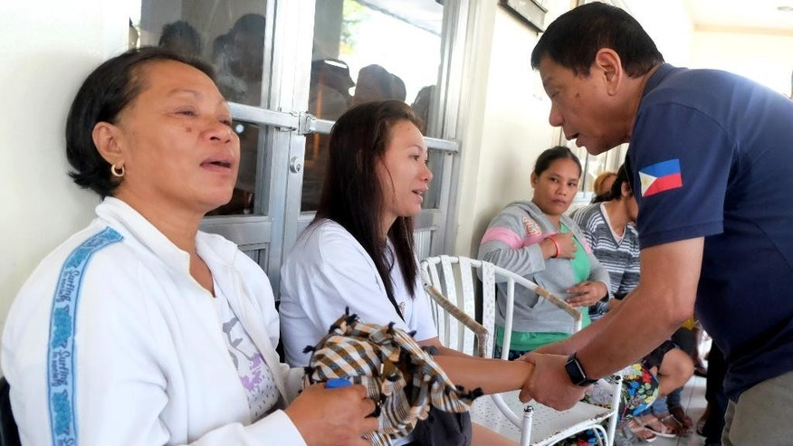 "In this photo released by Malacanang Palace Presidential Communications Operations Office Presidential Photographers Division, Philippine President Rodrigo Duterte, right, comforts a victim outside a hospital where people injured in Friday's explosion at a night market were brought in in Davao city, his hometown, Saturday, Sept. 3, 2016 in southern Philippines. Duterte declared a nationwide ""state of lawlessness"" Saturday after suspected Abu Sayyaf extremists detonated a bomb at the market. (Kiwi Bulaclac/Malacanang Palace Presidential Communications Operations Office Presidential Photographers Division via AP)"
