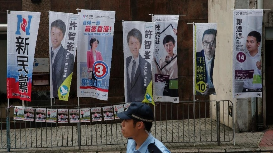 A police officer stands near a polling station for the legislative council election Sunday, Sept. 4, 2016. Polls opened in Hong Kong Sunday for the specially administered Chinese city's most crucial election since the handover from Britain in 1997. The vote for lawmakers in the Legislative Council is also the first since 2014 pro-democracy street protests rocked the Asian financial hub. (AP Photo/Vincent Yu)