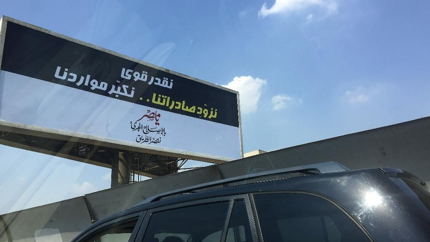 """A motorist drives past a government billboard in Cairo, Saturday, Sept. 3, 2016, which reads in Arabic: """"We sure can ... boostour exports andincreaseour resources. Oh, Egypt, With bold reforms, weshorten the road."""" Billboards and street signs have gone up across Egypt's capital extolling austerity and hope, part of a pro-government public relations campaign aimed at preparing Egyptians for sweeping economic reforms. (AP Photo/Hamza Hendawi)"""
