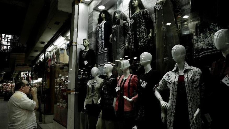 FILE -- In this Wednesday, Aug. 9, 2016 file photo, a man looks at a women's boutique with discounted prices attached to the clothes in downtown Cairo, Egypt. Hundreds of giant billboards and street signs have gone up in Egypt's capital bearing messages of austerity and hope seemingly designed to prepare Egyptians for sweeping economic reforms. Witnesses say the advertisements, which are concentrated in the heart of the capital and on its main artery roads, went up on Friday, Sept. 2, 2016. (AP Photo/Nariman El-Mofty, File)
