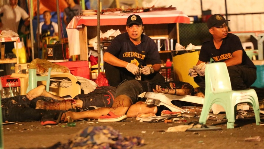 Philippine police investigators check bodies at a blast site at a night market that has left at least several people dead and wounded others in southern Davao city, Philippines