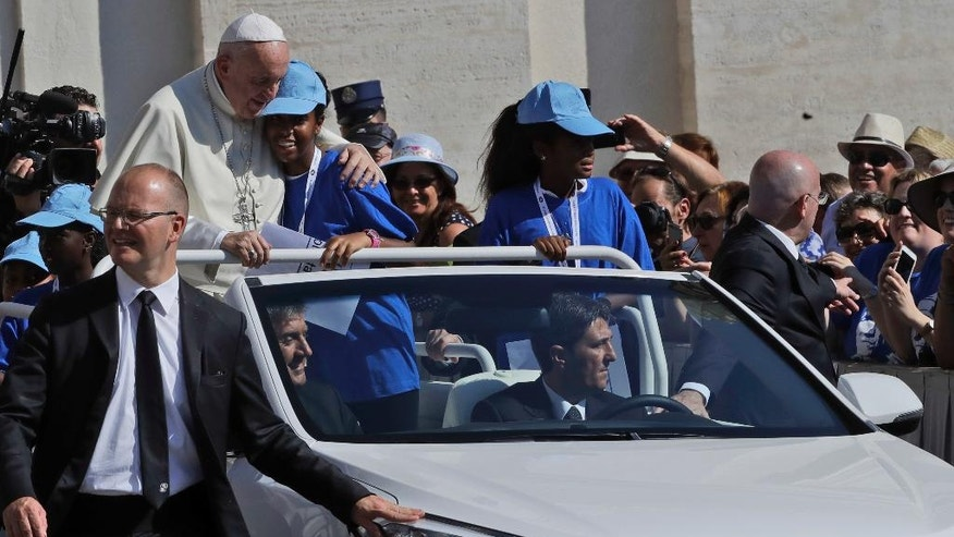 Pope Francis hugs a girl on his pope mobile upon his arrival in St. Peter's Square at the Vatican for a jubilee audience for workers and volunteers of mercy, Saturday, Sept. 3, 2016. The square hosts a ceremony Sunday expected to draw hundreds of thousands of admirers of Mother Teresa, a nun who before her death in 1997, cared for the destitute who were dying in the streets of India.  (AP Photo/Alessandra Tarantino)