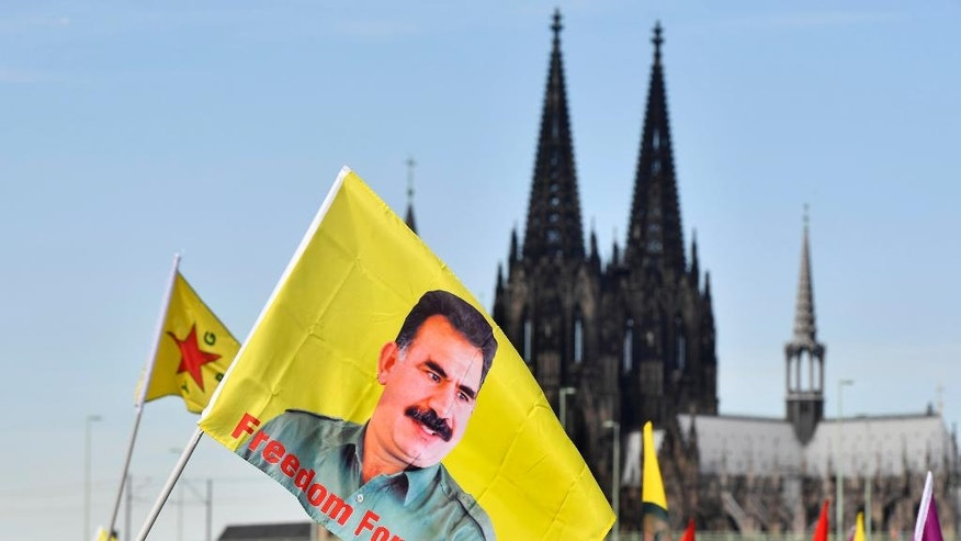 "Thousands of Kurds, including many carrying flags with the image of jailed PKK leader Abdullah Ocalan, demonstrate in Cologne, Germany, Saturday, Sept. 3, 2016. Organizers say Saturday's demonstration is aimed in part at protesting against Turkey's military intervention in northern Syria and what they call the ""dictatorial"" behavior of Turkish President Recep Tayyip Erdogan. In background the Cologne cathedral.  (AP Photo/Martin Meissner"