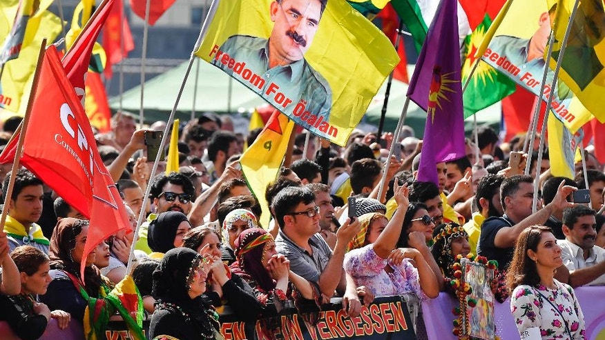 "Thousands of Kurds, including many carrying flags with the image of jailed PKK leader Abdullah Ocalan, demonstrate in Cologne, Germany, Saturday, Sept. 3, 2016. Organizers say Saturday's demonstration is aimed in part at protesting against Turkey's military intervention in northern Syria and what they call the ""dictatorial"" behavior of Turkish President Recep Tayyip Erdogan.  (AP Photo/Martin Meissner"