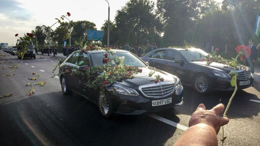 People throw flowers on limousines as they gather along a road to watch the funeral procession of President Islam Karimov in Tashkent, Uzbekistan, early Saturday, Sept. 3, 2016. Karimov has died of a stroke at age 78, the Uzbek government announced Friday. (AP Photo/Umida Akhmedova)