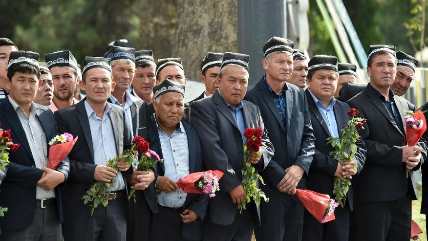 People hold flowers as they gather along the road to watch the funeral procession of President Islam Karimov in Samarkand, Uzbekistan, Saturday, Sept. 3, 2016. Karimov has died of a stroke at age 78, the Uzbek government announced Friday. Karimov will be buried Saturday in the ancient city of Samarkand, his birthplace, the government said in a statement. (AP Photo)