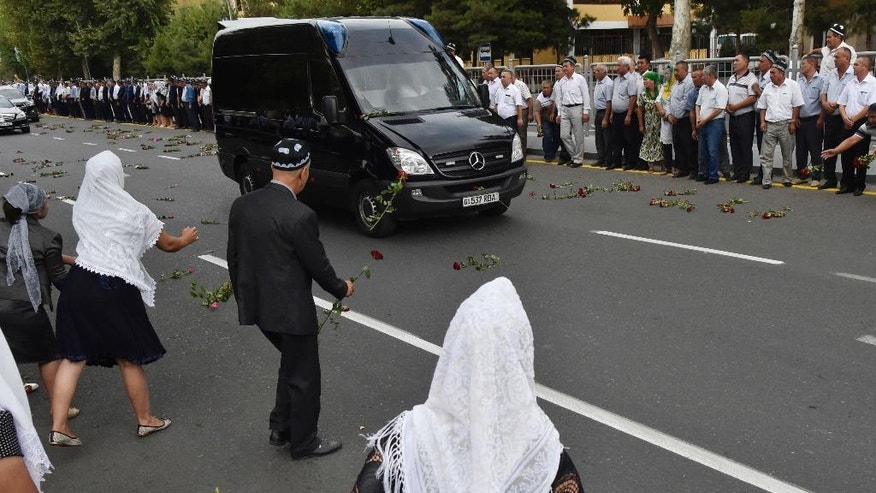 People throw flowers on the hearse as they gather along the road to watch the funeral procession of President Islam Karimov in Samarkand, Uzbekistan, early Saturday, Sept. 3, 2016.  Karimov has died of a stroke at age 78, the Uzbek government announced Friday. Karimov will be buried Saturday in the ancient city of Samarkand, his birthplace, the government said in a statement. (AP Photo)